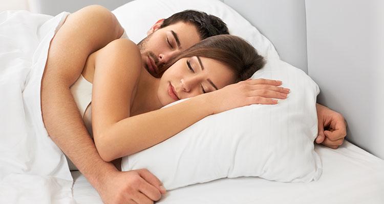 Um homem abraça uma mulher na cama